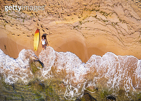 Aerial view of a surfer girl resting on a beach. - gettyimageskorea