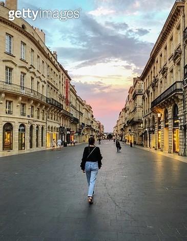 Rear View Of Woman Walking On Street Amidst Buildings In City - gettyimageskorea