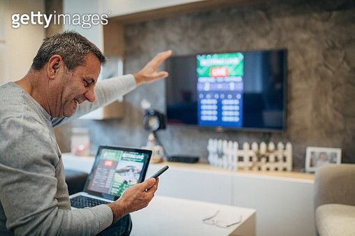 Mature man using mobile app for live betting and online gambling and watching a sports match - gettyimageskorea