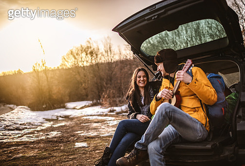 Yong couple playing a guitar in car trunk - gettyimageskorea