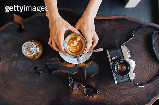 coffee on the table, next to a smartphone and an analog, vintage camera or just a modern mirrorless camera in a vintage retro silver body. - gettyimageskorea