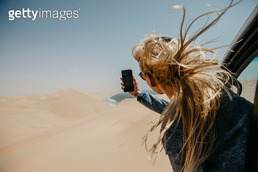 Namibia, Walvis Bay, Namib-Naukluft National Park, Sandwich Harbour, woman leaning out of car window taking cell phone picture - gettyimageskorea