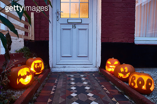 Carved pumpkins lining a path up to a door of a house on halloween. The pumpkins have been carved and are lit. - gettyimageskorea
