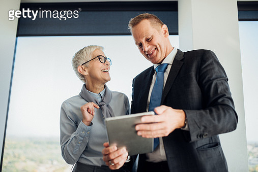 Business couple looking at digital tablet at work - gettyimageskorea