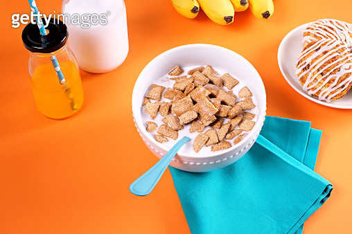 Breakfast scene with bowl of cereal, juice, milk, bananas and pastries on orange background - gettyimageskorea