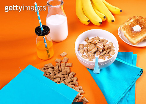 Breakfast scene with spilled cereal, bowl of cereal, juice, milk, bananas, and toast on orange background - gettyimageskorea