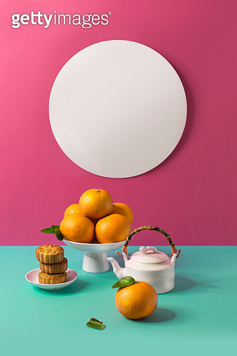 A pile of tangerine and tea served on vibrant coloured background. Text space image. - gettyimageskorea