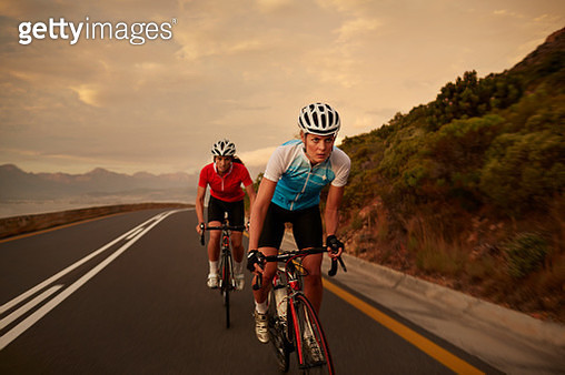 Professional female cyclists on road bikes at sunset - gettyimageskorea