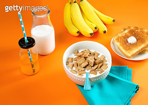 Breakfast scene with bowl of cereal, juice, milk, bananas and toast on orange background - gettyimageskorea