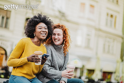Photo of two female friends on the street holding smart phone and credit card - gettyimageskorea