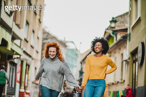 Photo of two female friends walking down the street and laughing - gettyimageskorea