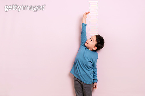 Child measuring his height on wall. He is growing up so fast. - gettyimageskorea