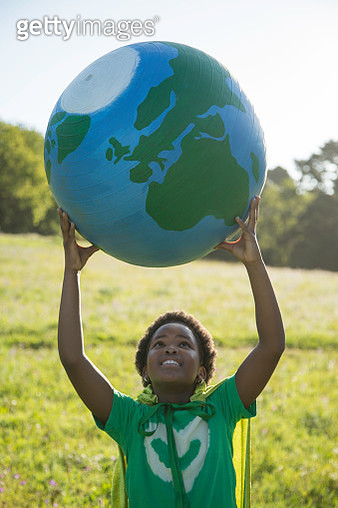 Young African girl holding up a pretend globe outdoors - gettyimageskorea