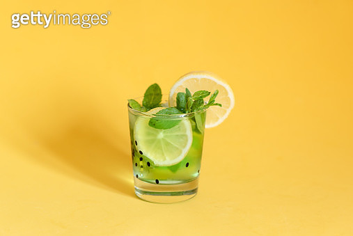 Fresh summer fruits water or lemonade with lemon, orange and mint on yellow background. Close up. - gettyimageskorea