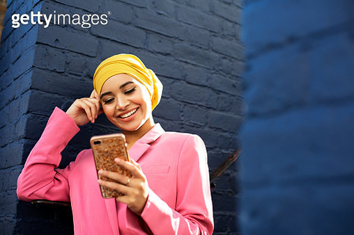 Young Muslim woman using phone - gettyimageskorea