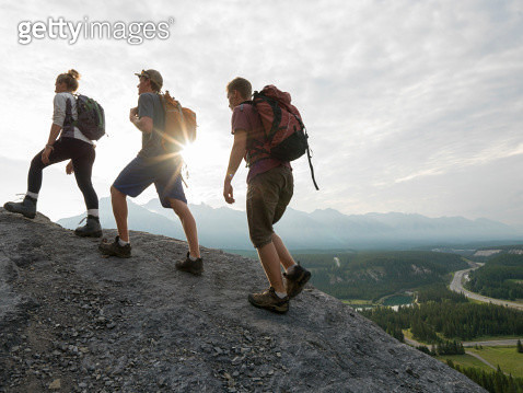 Hikers climb ridge above sunrise, valley - gettyimageskorea