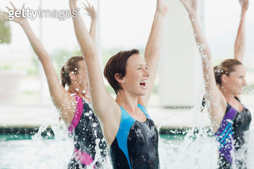 Enthusiastic women jumping in swimming pool - gettyimageskorea