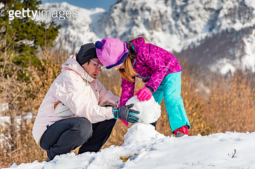 Grandmother and Daughter Making a Snowman in Mountains - gettyimageskorea