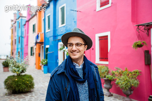 Young smiling happy man in glasses and hat among colorful houses of Burano, Italy - gettyimageskorea