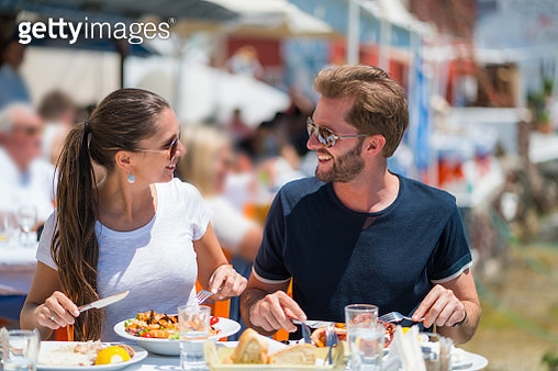 romantic couple eating their dinner or lunch while sightseeing on typical setting in greece. greek fish and seafood served in rural surrounding - romantic travel vacation series - gettyimageskorea