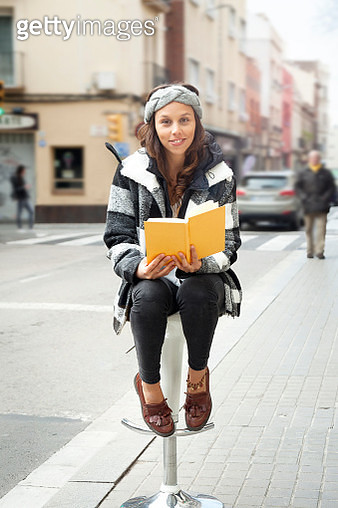 Young woman reading on the street - gettyimageskorea