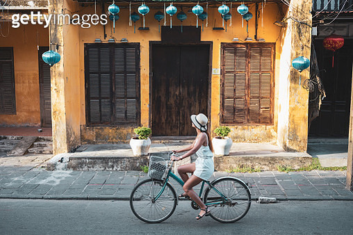 Woman tourist cycling in the old district of Hoi An in Vietnam during day . - gettyimageskorea