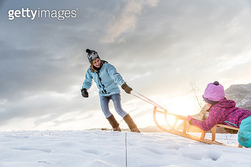 Cheerful Mother and Daughter Having Fun With Sled on a Hill - gettyimageskorea