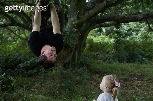 Father climbing a tree hanging from a branch while his toddler daughter watches - gettyimageskorea
