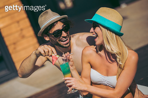 Affectionate couple enjoying summer day drinking cocktail and flirting - gettyimageskorea