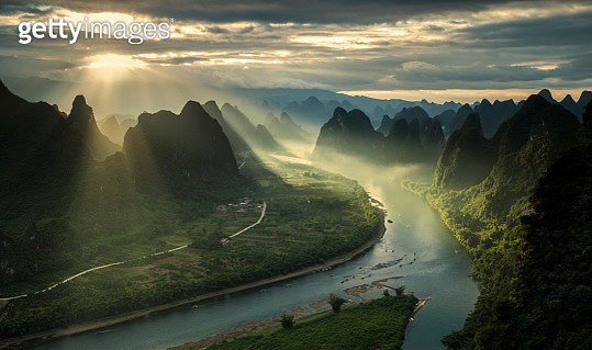 Sun beams on a misty morning on karst mountains and river Li in Guilin/Guangxi region of China - gettyimageskorea