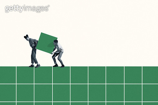 Woman and man carrying large green block on grid - gettyimageskorea