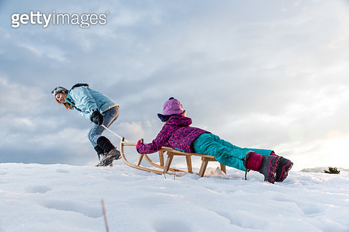 Mother and Daughter Having Fun With Sled on a Hill - gettyimageskorea