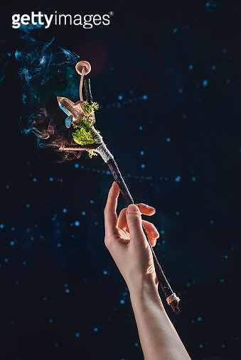 Magic wand in the hand of a witch on a dark background, nature and occult concept - gettyimageskorea