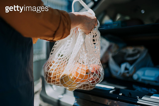 an asian chinese  female delivery person getting the groceries and fruit her customer order online shopping in recycle bags from her car trunk and deliver it to her customer - gettyimageskorea
