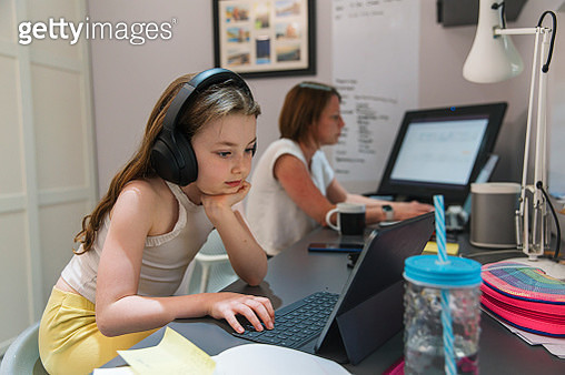 Young girl remote schooling in study. Mother is working in the background - gettyimageskorea