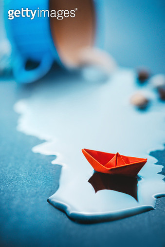 Cup with spilled water and red paper boat, poetic concept, travel still life - gettyimageskorea