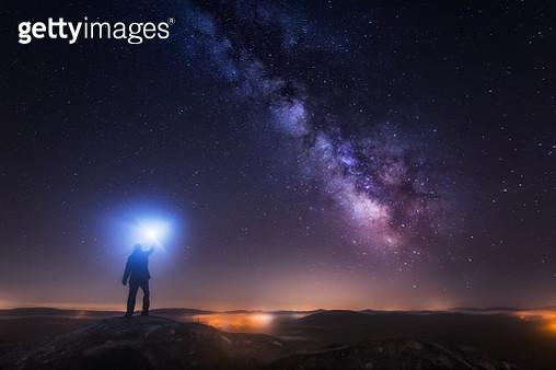 A young man on a mountain watching the Milky Way and lightning with a flash. Taken in Vimianzo, A Coruña - gettyimageskorea