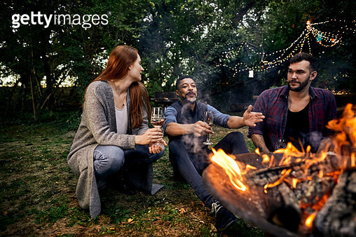 Three people sitting at campfire on a garden party - gettyimageskorea