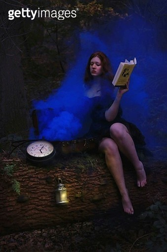 Young Woman With Book Sitting Amidst Blue Smoke - gettyimageskorea