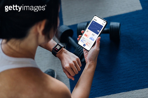 Over the shoulder view of young active woman using exercise tracking app on smartphone to monitor her training progress after exercising at home - gettyimageskorea