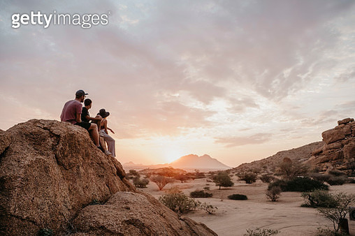 Namibia, Spitzkoppe, friends sitting on a rock watching the sunset - gettyimageskorea