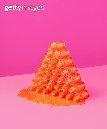 Still life image of a pyramid made of orange nail varnish bottles shot on a pink background. - gettyimageskorea