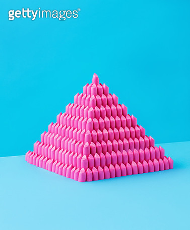 Still life image of a pyramid made of pink lipstick bullets shot on a blue background. - gettyimageskorea