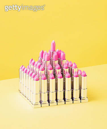 Still life image of a pyramid made of pink lipsticks shot on a yellow background. - gettyimageskorea