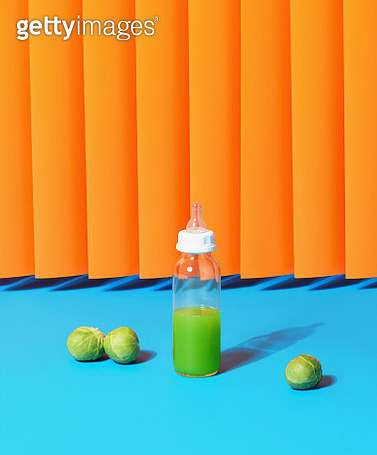 Still life image of a baby bottle containing green juice surrounded by brussels sprouts shot against a blue and orange background. - gettyimageskorea