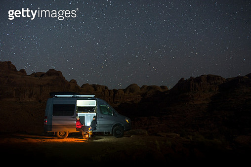 A man and woman sitting in their van under the desert night sky - gettyimageskorea
