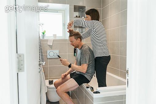 Women cutting partner's hair in the bathroom - gettyimageskorea