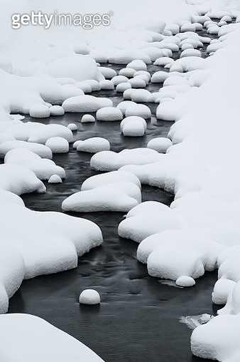 Close up of riverbed with snow-covered rocks in winter. - gettyimageskorea
