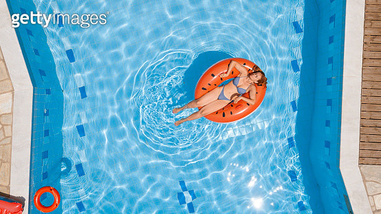 Mid adult woman in bikini enjoying on watermelon inflatable ring in the pool - gettyimageskorea