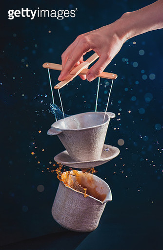 Skilled barista with ceramic pour-over, pitcher and coffee splashes, puppet master concept - gettyimageskorea